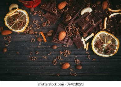Chocolates background. Chocolate. Cup of hot chocolate, lemon, nuts and assortment of fine chocolates in dark, and milk chocolate on dark wooden table