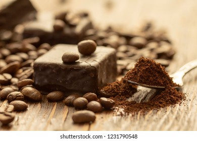 Chocolates and coffee seeds on wooden background