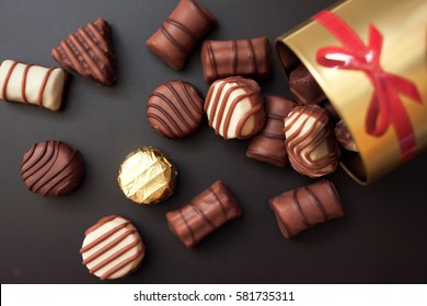 Chocolates in different shapes and colors spilled from the gold round box with a red bow on a black background. among all the sweets have a gold-wrapped in the color of the box