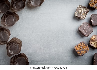 Chocolates and empty wrappers on a stone background