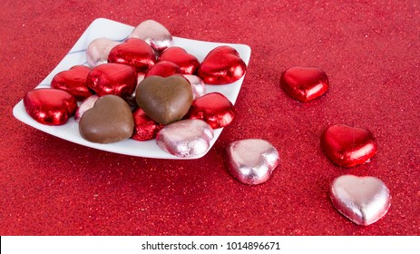 Chocolates heart shape wrapped in red and light pink foil, Valentine's Day backgrounds.