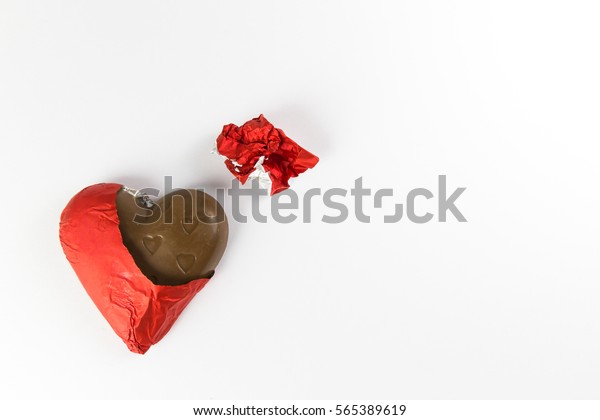 Chocolates heart shape wrapped in red foil for give to valentine day is open wrap,isolated