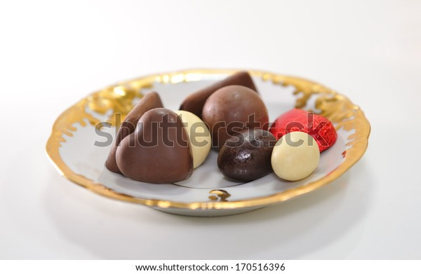 Chocolates of various forms on the golden saucer.