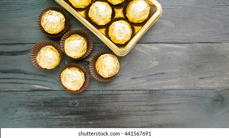 Chocolates wrapped in foil on black wooden