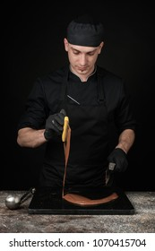 Chocolatier in black uniform in the process of making chocolates. Making sweets. Photo in studio, on a black background.