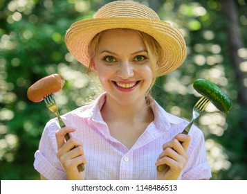Choice between meat or vegetables. Girl smiling face holds forks with sausage and cucumber. Alternative nutrition for vegetarians. Vegetarians nutritional choice. Vegetarian lifestyle is her choice.