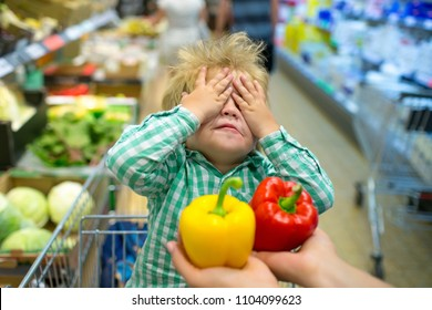 Choice blindly. Hide and seek. Shopping with children. Pepper. Red or yellow pepper. Vegetables in store. Child in shopping cart. No appetite. Vegetable diet. Funny baby dont want eat healthy food