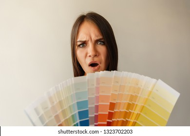Choice of color for painting wall with color palette. Crazy emotion of woman