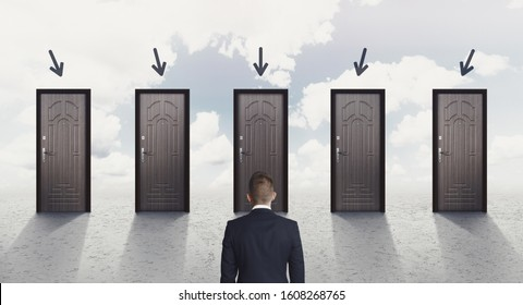 Choice concept. Rear view of businessman choosing the right door, each door indicated with arrow over sky background, panorama