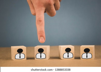 Choice of an employee leader from the crowd. the hand points to the wooden cube that symbolizes that the hand makes the choice.
