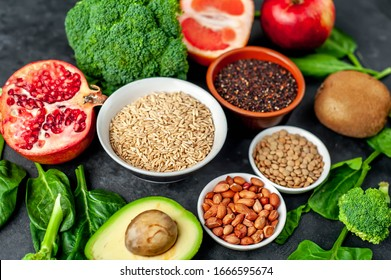 The choice of healthy food: fruits, seeds, cereals, superfoods, vegetables, leafy vegetables on a stone background. Healthy food for humans.
