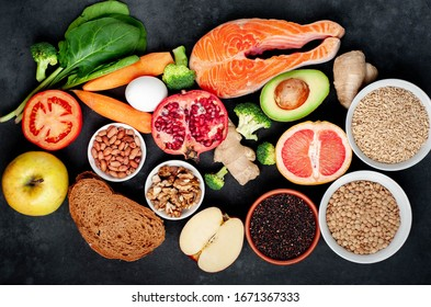 The choice of healthy food: salmon, fruits, seeds, cereals, superfoods, vegetables, leafy vegetables on a stone background. Healthy food for people.