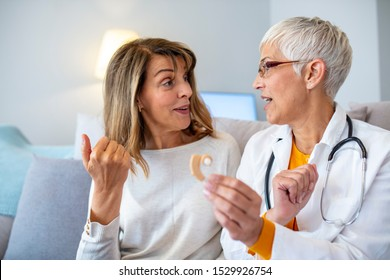 The choice of hearing aid in the doctor's office. Doctor showing hearing aid. Doctor giving hearing aid to patient. The hearing aid for a senior woman