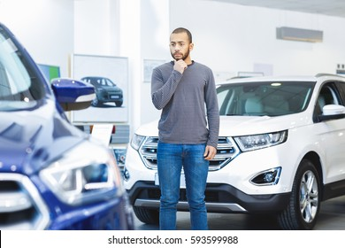 Choice to make. African man choosing a new car at the dealership standing between two vehicles looking confused decision choice buying choosing transport driver buyer consumer client consumerism