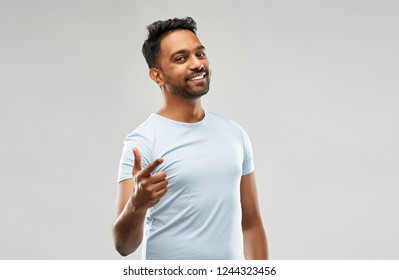 choice and people concept - smiling young indian man pointing finger at you over grey background