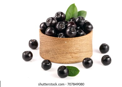 Chokeberry with leaf in wooden bowl isolated on white background. Black aronia berries