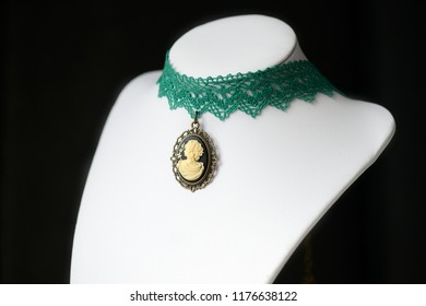 Choker necklace with girl cameo pendant on a dark background close up