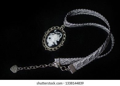 Choker necklace with skull cameo pendant on a dark background close up