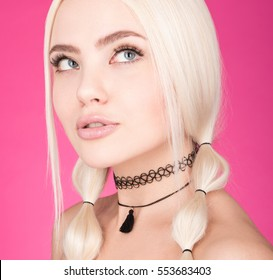 The choker on the neck. Closeup beauty portrait of young beautiful woman with white hair. Studio shot on pink background