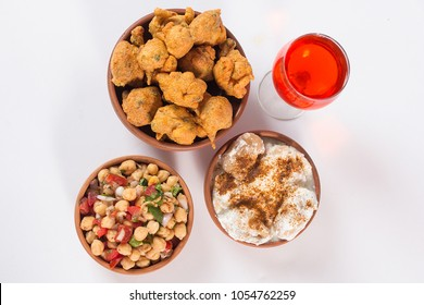 Chola chana chaat and Basin Pakora with dahi barey, Popular indian or pakistani street food, Traditional ramadan food, Delicious ramzan iftar meal with glass of red juice on white background.