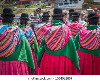 Cholitas, wearing pink pleated skirts, green shawls and black bowler hats parade in a Day of the Sea commemoration in Copacabana, Bolivia. They carry colourful striped blanket bags on their shoulders.
