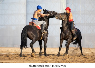 Cholpon-Ata city, Kyrgyzstan - Sep 5, 2018: Two men competing in er-enish (traditional Kyrgyz horsemen wrestling) match during 2018 World Nomad Games.