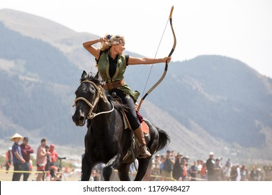 Cholpon-Ata city, Kyrgyzstan - Sep 6, 2018: Female archer aiming at a target during a traditional horseback archery competition.