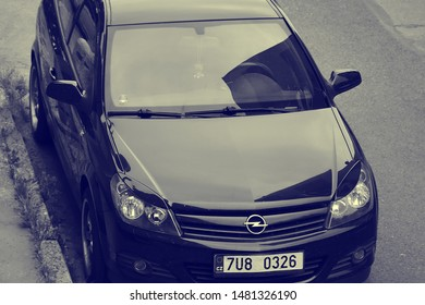 Chomutov, Czech republic - August 17, 2019: black car Opel Astra parked in street during sommer cloudy weather with yellow blue stylization