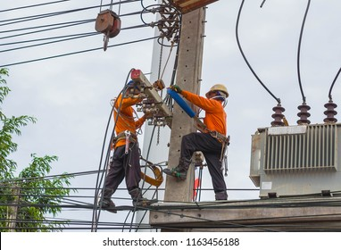 Chon Buri, Thailand 16 August 2018 Two electricians are repairing high voltage wires. On large high-voltage power poles and with high voltage cables around