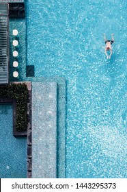 CHON BURI, THAILAND. MAR 7, 2018: Top view of swimming pool with floating bar and a man swimming in summer.