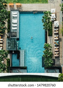 CHON BURI, THAILAND. MAR 7, 2018: Top view of swimming pool with floating bar, people lay down on the beach chairs and a man swimming in summer.