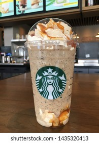Chon buri,Thailand/Chon buri  May 7, 2018 : Starbucks coffee The Dark Caramel Coffee Frappucino  with Java chip on wood table in Starbucks coffee shop.