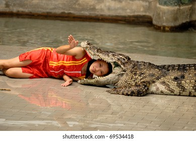 CHONBURI - DECEMBER 5: A girl is performing a show with a live crocodile on December 5, 2010 in Sriracha Zoo, Chonburi, Thailand