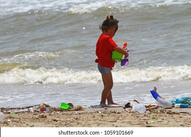 Chonburi Mar 15 : Young girl in red shirt playing on dirty beach at Bang Sean, Chonburi, Thailand on March 15, 2018.