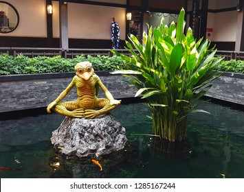 Chonburi, TH - DECEMBER 27, 2018: The statue of golden Kappa, the famous Japanese monster, that decorating at a wide natural pond, near the Japanese style building.