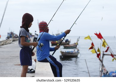 CHONBURI, THAILAND - 30th OCTOBER 2016; Fisherman family are catching fish at pier around fisherman village area at Bangsaen beach, Chonburi.