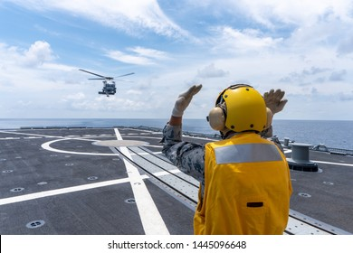 CHONBURI, THAILAND - APRIL 10, 2019:  Signal man gives the hand signal to Sikorsky MH-60S Seahawk helicopter to land on the flight deck of the HTMS. Bhumibol Adulyadej stealth frigate of Thai navy