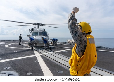 CHONBURI, THAILAND - APRIL 10, 2019: Sailors are going to chalk and chain a Sikorsky MH-60S Seahawk helicopter  to the flight deck of the HTMS. Bhumibol Adulyadej stealth frigate of Royal Thai navy.