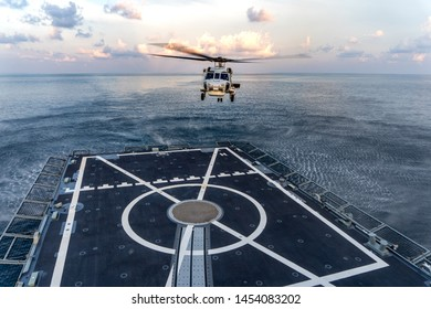 CHONBURI, THAILAND - APRIL 10, 2019:  Sikorsky MH-60S Seahawk helicopter prepare to land on the flight deck of the HTMS. Bhumibol Adulyadej stealth frigate of Royal Thai navy in the evening
