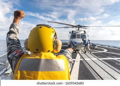 CHONBURI, THAILAND - APRIL 10, 2019: Signal man orders sailors to chalk and chain the Sikorsky MH-60S Seahawk helicopter  on the flight deck of the HTMS. Bhumibol Adulyadej frigate of Royal Thai navy.
