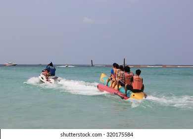 Chonburi, Thailand - February 11, 2012: Tourists are having fun riding banana boat at Tawaen Beach, the most developed and the most visited beach on Koh Larn.