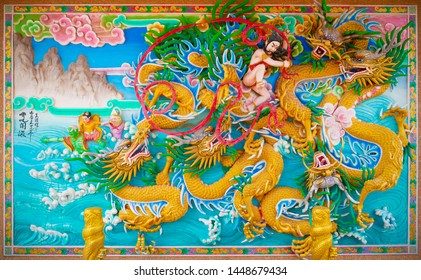 Chonburi, Thailand - July 12, 2019: Nezha god of honour fighting with dragons low and high relief art in Chinese temple.
