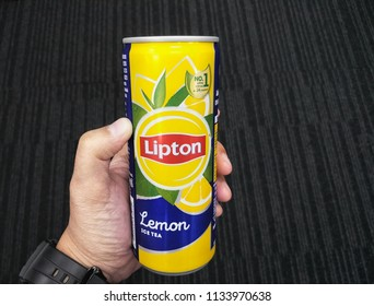 Chonburi, Thailand - July, 13 2018:Hand hold aluminium can of Lipton ice tea with lemon on black background.