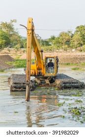 CHONBURI , THAILAND - MARCH 16 ,2016 : The dirty backhoe working in mud lake, iron digger into water in the morning in Sattahip Chonburi, Thailand on March 16, 2016