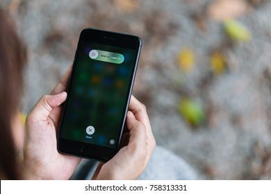 Chonburi, Thailand - November 19, 2017 : Apple iPhone 8 Plus showing slide to power off on screen. It was held by woman hand.
