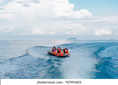 Chonburi, Thailand - November 26, 2013 :: Tourists on water attraction donut boat during summer vacations