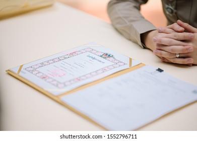 Chonburi, Thailand / Pattaya 10 - 10 -  2019 : Thai Registrar certifying spouse's marriage registration. bride and groom register marriage.