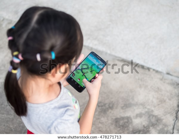 Chonburi, Thailand- September 2, 2016: Asian little girl playing a Pokemon Go game outdoors. Pokemon Go is a popular virtual reality game for mobile devices