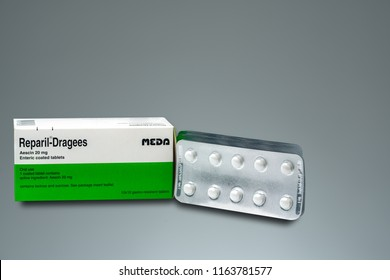 CHONBURI, THAILAND-AUGUST 3, 2018 : Reparil-Dragees. Aescin 20 mg enteric coated tablets product of Meda Pharma (Thailand). Manufactured by Madaus GmbH, Germany. White round tablets isolated on grey.