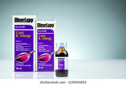 CHONBURI, THAILAND-OCTOBER 14, 2018 : Dimetapp Elixir in amber bottle with measuring cup and packaging isolated on gradient background. Nasal decongestant and antihistamine drug. Medicine for cold.